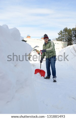 Man shoveling snow on a sidewalk after a snow storm - stock photo
