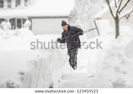 Man shoveling snow (shallow depth of field, focus on snow in foreground) - stock photo