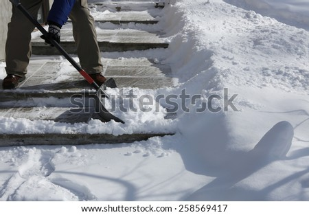 Man shoveling the show on bright winter day - stock photo