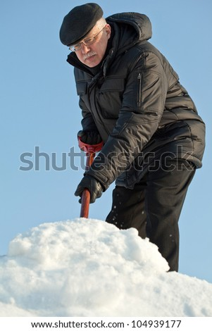 Man shovelling fresh snow from a road after hard snowfall - stock photo