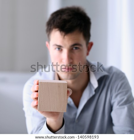 Man showing a wooden cube - stock photo