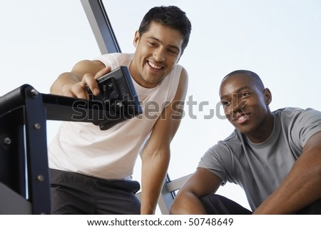 Man showing another man how to use control panel of exercise machine - stock photo