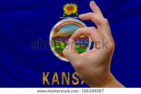 man showing excellence or ok gesture in front of complete wavy american state flag of kansas symbolizing best quality, positivity and success - stock photo