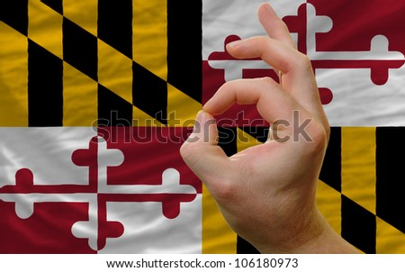 man showing excellence or ok gesture in front of complete wavy american state flag of maryland symbolizing best quality, positivity and success - stock photo