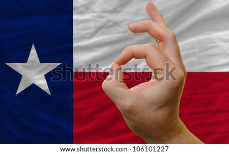 man showing excellence or ok gesture in front of complete wavy american state flag of texas symbolizing best quality, positivity and success - stock photo