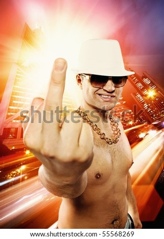 Man showing middle finger in front of night city - stock photo