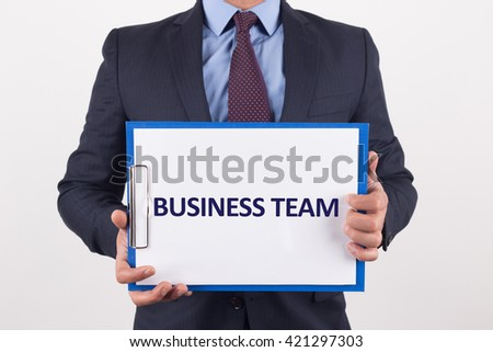 Man showing paper with BUSINESS TEAM text - stock photo
