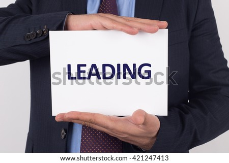 Man showing paper with LEADING text - stock photo