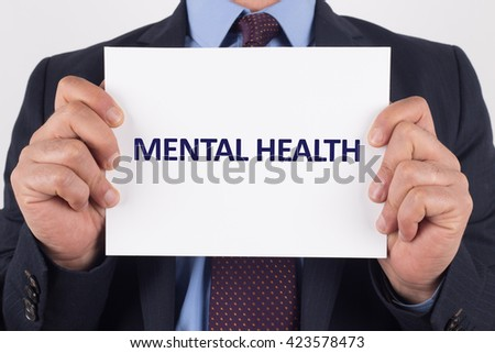 Man showing paper with MENTAL HEALTH text - stock photo