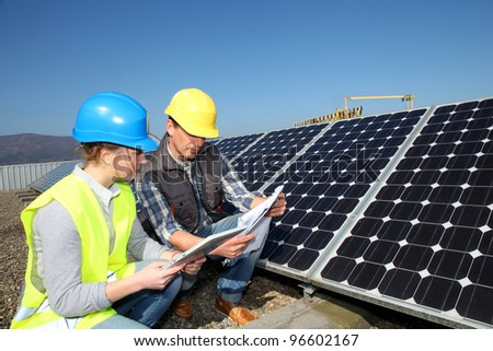 Man showing solar panels technology to student girl - stock photo