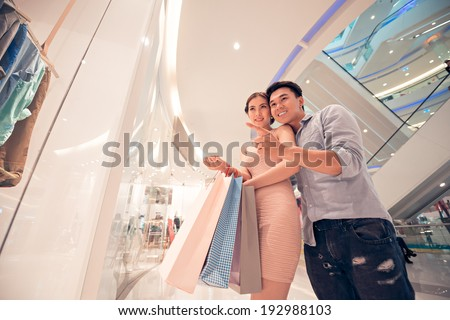 Man showing something in the shop window to his wife - stock photo