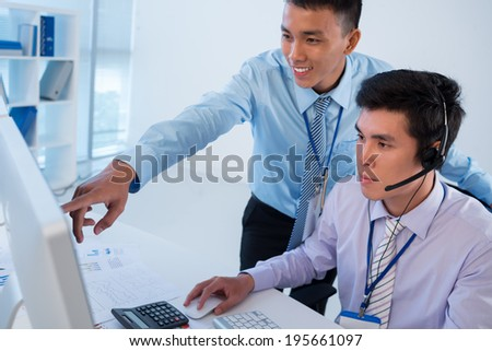 Man showing something on the screen to his colleague - stock photo