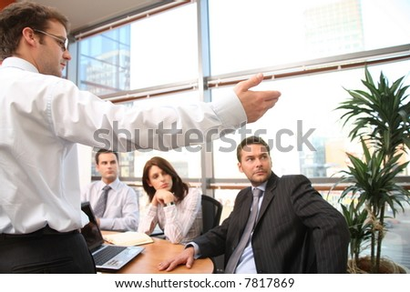 man  showing the results  to the group of business people at the meeting - stock photo