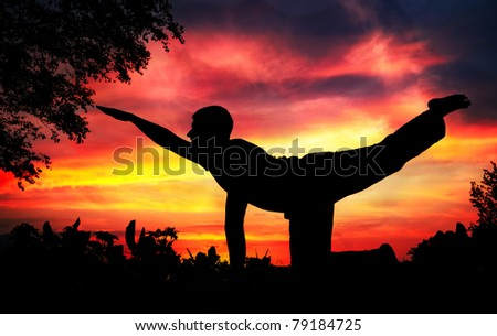 Man silhouette doing parshva marjariasana cat pose with tree nearby outdoors at red sunset background - stock photo