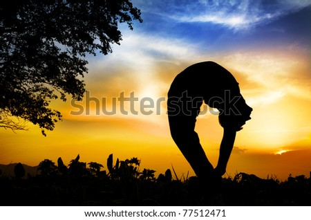 Man silhouette doing tiriang mukhottanasana backward bending pose with tree nearby outdoors at sunset background - stock photo