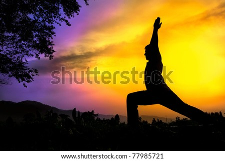 Man silhouette doing virabhadrasana I warrior pose with tree nearby outdoors at sunset background - stock photo