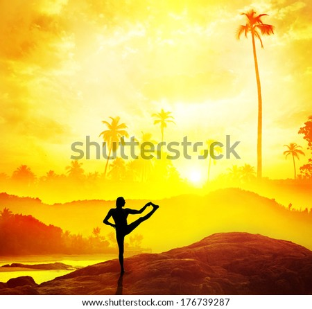 Man silhouette doing Yoga in tropics near the water at sunset in India - stock photo