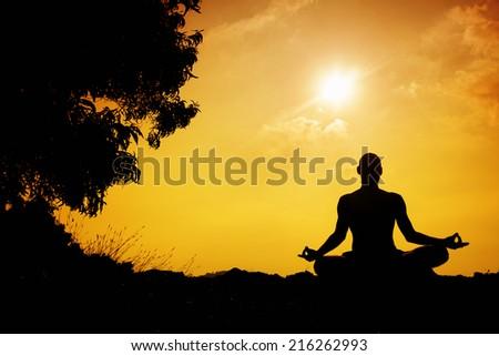 Man silhouette in Yoga meditation pose near the tree at sunset in Gokarna, Karnataka, India - stock photo