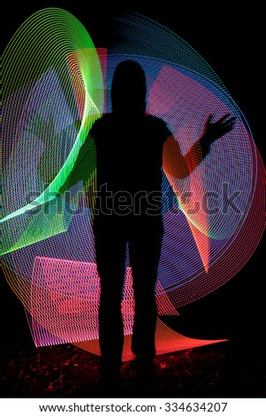 Man silhouette on colorful background made with light painting or light drawing photographic technique. Light drawing photo made by moving lights during long exposure - stock photo