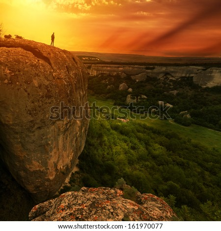 man silhouette on edge of rock with sunset sky on background - stock photo