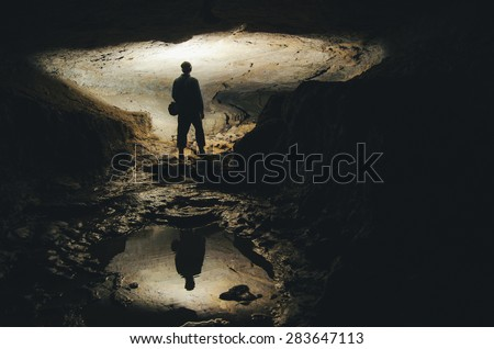 man silhouette reflecting in water in dark cave - stock photo