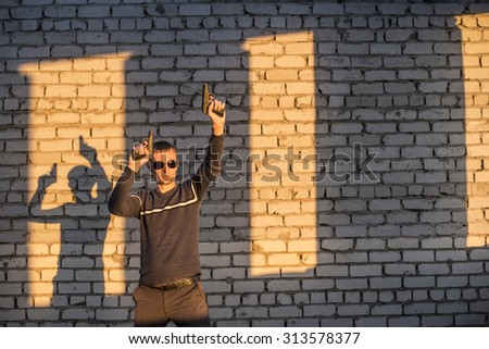 man silhouette with two gun Gay stand with a pistol in his hand with shadow  on brick wall background - stock photo