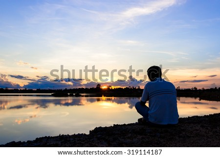 man sit down and take photo by camera at lake with sunset sky. - stock photo