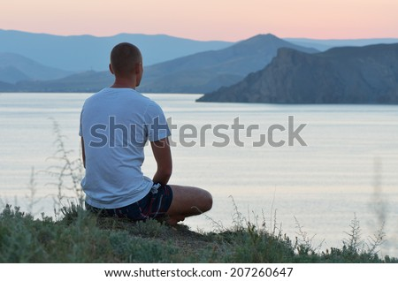 Man sits on a cliff above the sea and watching the sunset. Warm evening on the coast - stock photo