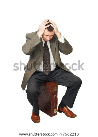 Man sits on the bag and seized hands for the head - stock photo