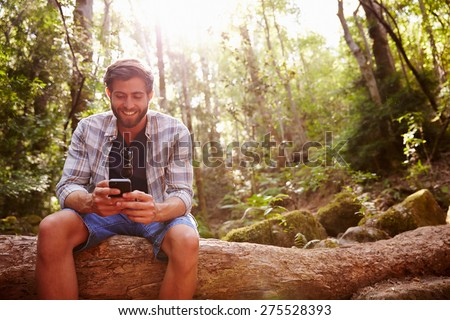 Man Sits On Tree Trunk In Forest Using Mobile Phone - stock photo