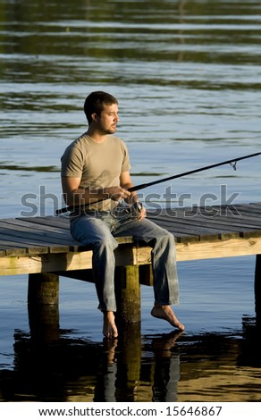 Man sitting and fishing on a dock in a bay as the sun is setting. - stock photo