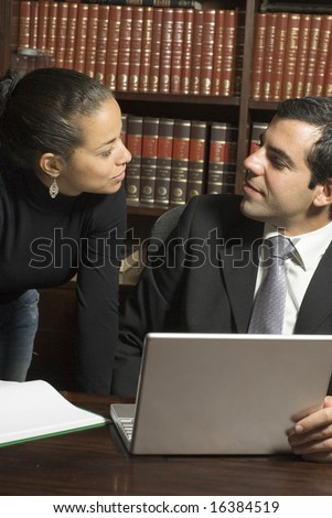 Man sitting at table in library looks at woman standing next to him. They are wearing suits and looking at each other. Vertically framed photo. - stock photo