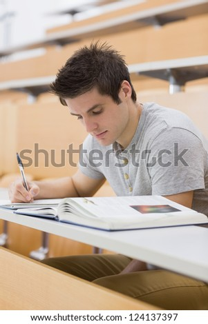 Man sitting at the lecture hall while writing - stock photo