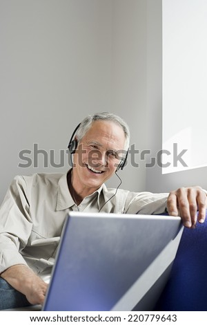 Man sitting by window wearing headphones, smiling and using a laptop - stock photo