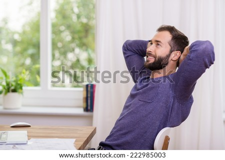Man sitting daydreaming at the office relaxing back in his chair with his hands behind his head staring up into the air with a contented smile - stock photo