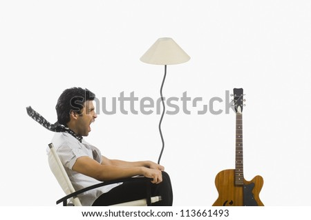 Man sitting in a chair and screaming - stock photo