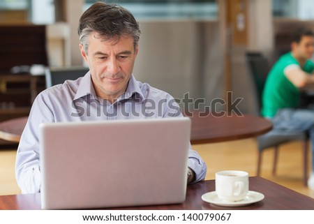 Man sitting in a coffee shop while drinking a cup of coffee and using a laptop - stock photo