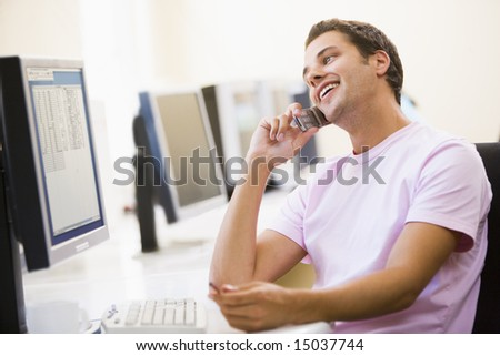 Man sitting in computer room using cellular phone and smiling - stock photo