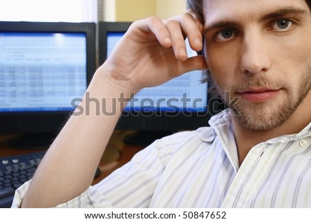 Man Sitting in Front of Computers, portrait. - stock photo