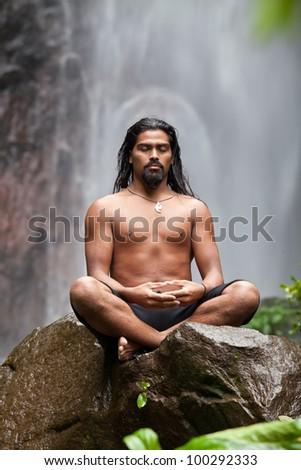 Man sitting in meditation on rock at waterfall in tropical rainforest - stock photo