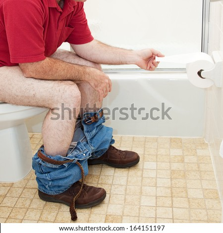 Man sitting in the bathroom on the toilet, pulling off a piece of toilet paper.   - stock photo
