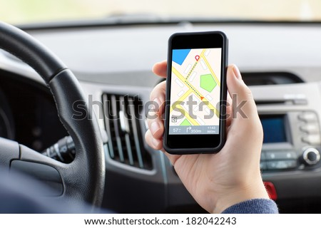 man sitting in the car and holding a touch phone with interface navigator on a screen  - stock photo
