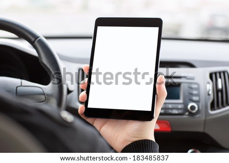 man sitting in the car, holding a touch tablet with an isolated screen. - stock photo