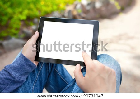 man sitting in the park and holding tablet computer with isolated screen - stock photo