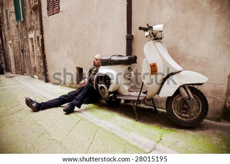 Man Sitting Near Retro Scooter. Perugia. Italy. - stock photo
