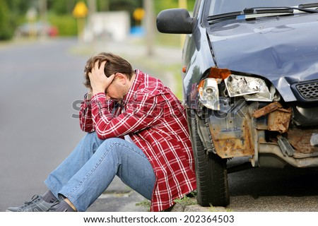 Man sitting near the car after accident - stock photo