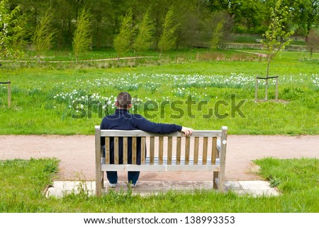 man sitting on a bench in a countryside scene - stock photo