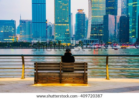 man sitting on a bench on The Bund looking at Shanghai financial district - stock photo