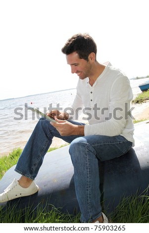 Man sitting on a lakeside with electronic tablet - stock photo