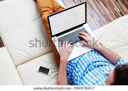Man sitting on a sofa and browsing the web - stock photo